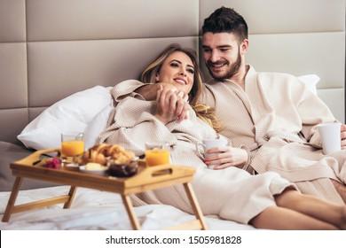 Junge glückliche Paare, die im luxuriösen Hotelzimmer frühstücken und fernsehen.
