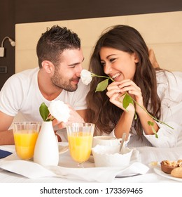 Young happy couple having breakfast in luxury hotel room.