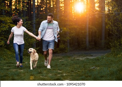 Young happy couple having fun in the forest at sunset. Enjoying time with their dog.
