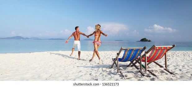 Young happy couple having fun on a tropical resort's white beach