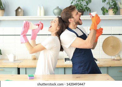 Young happy couple is having fun while doing cleaning and singing at home.