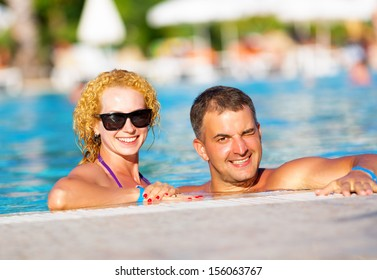 Young happy couple having fun in the pool