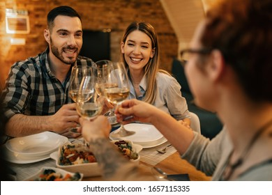 Young happy couple having fun while toasting with friends during dinner at dining table.