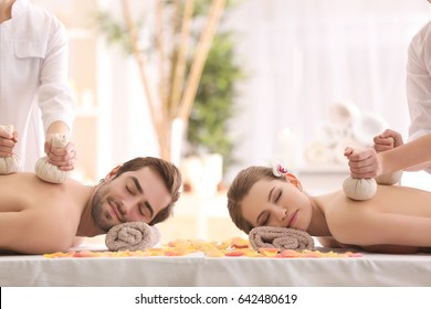 Young happy couple having massage in spa salon