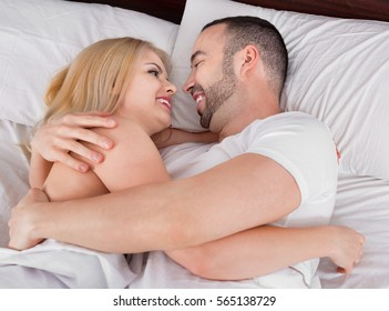 Young happy couple having sex in comfortable family bed