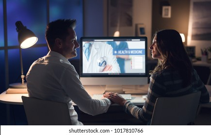 Young happy couple holding hands and searching medical services online, healthcare and telemedicine concept