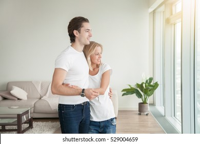 Young happy couple, holding a key, purchased a new apartment, rather than throw money away on rent, flat as the biggest investment, planning a future, preparing a housewarming party