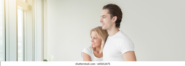 Young happy couple, holding a key, purchased a new apartment, planning a future, preparing a housewarming party. Horizontal photo banner for website header design with copy space for text