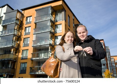 Young happy couple holding keys to their new home