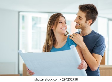 Young happy couple holding a project and planning their new house, relocation and renovation concept