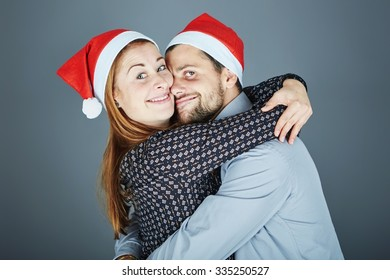 young happy couple hug and love christmas in front of grey background
