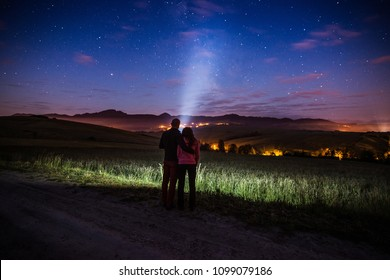 Young happy couple hugging at starry night in mountains. Pointing flashlight light to the sky. Freedom and relax concept