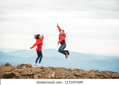 Young happy couple jumping in the background of the mountain. guy girl jumping happy in the mountains with a breathtaking view. in red clothes. Valentine's Day. stand with your back