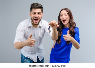 Junges glückliches Paar mit Schlüssel einzeln auf grauem Hintergrund. Mann und Frau haben eine Wohnung bekommen