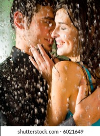Young happy couple kissing and hugging under a rain