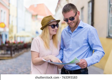 young happy couple looking at city map