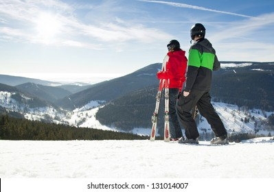 Young happy couple looking in snowy mountains holding ski, Czech