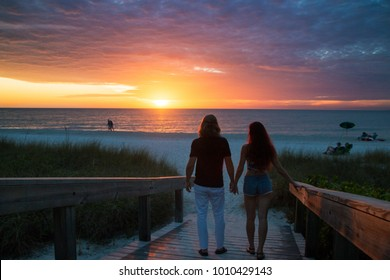 Young happy couple in love holding hands and walking towards the exotic sandy beach while romantic sunset, silhouettes of man and woman in front of impressive beautiful sunset sea view