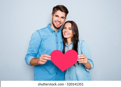 Young happy couple in love holding red paper heart.