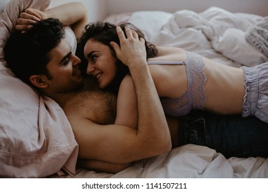 Young happy couple in love lying on bed and enjoying each other