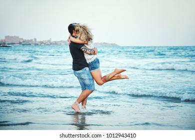 Young happy couple in love outdoors. loving man and woman walking on sea shore