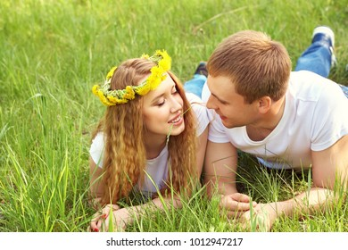 Young happy couple in love outdoors. loving man and woman in a wreath of dandelions lying in the grass