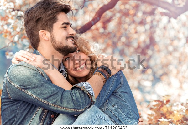 Young happy couple in love outdoors.Loving man and woman  in a spring blooming park.