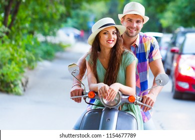 Young happy couple in love riding a vintage scooter in the street wearing hats. Holiday and travel concept