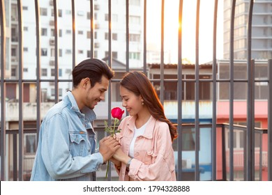 young happy couple love and romantic at first date relationship. asian teenage woman surprise and smiling at boyfriend gives red rose flowers at dinner in valentine day. couple and happiness concept.
