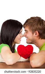 Young happy couple love smiling, looking to each other and hug hold a red heart touching nose, sitting on th couch isolated over white background
