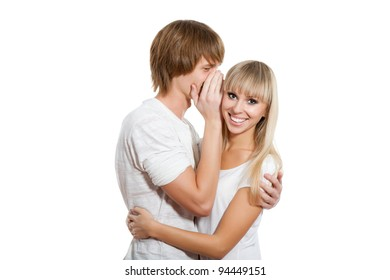 Young happy couple love smiling, man telling a secret to a girl - she is looking at camera laughing, isolated over white background