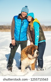 Young happy couple in love with St. Bernard dog in the winter outdoors