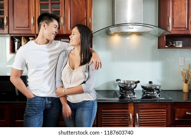 Young happy couple in love standing in kitchen and looking at each other
