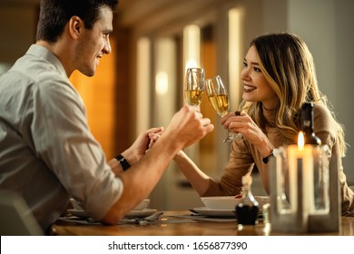 Young happy couple in love toasting with champagne while holding hands at dining table. Focus is on woman.