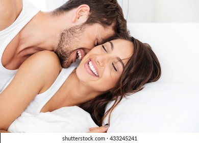 Young happy couple lying together in bed