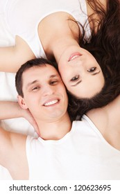 Young happy couple lying in the white bed