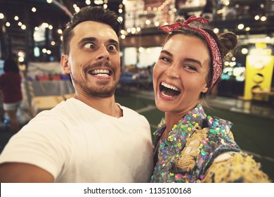 Young  and happy couple is making funny faces at evening street