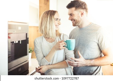 Young happy couple, man and woman, cooking food together in kitchen and making coffee
