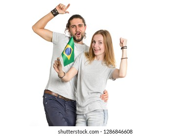 Young happy couple, man and woman, with the Brazil flag in their hands isolated on white background. People -football fans.