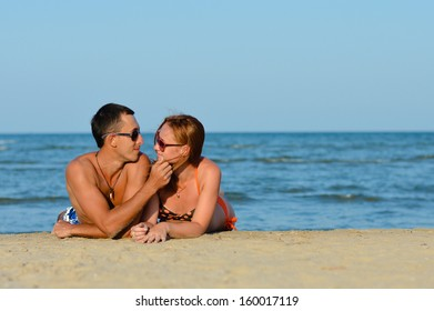 Young happy couple man and woman enjoying lying on sandy beach on summer outdoors background