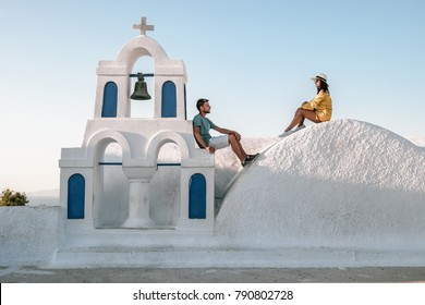 Young happy couple man and woman at a greek church in Oia Thira Cyalides Santorini Greece
