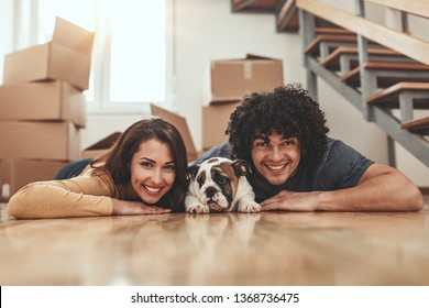 The young happy couple is moving into a new house. They are lying down on the floor and hugging their little puppy after they brought boxes with things to their new home.