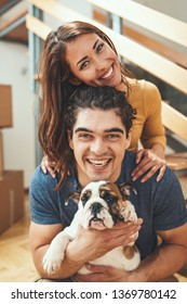 The young happy couple is moving into a new house. They are holding their little puppy after they brought boxes with things to their new home.