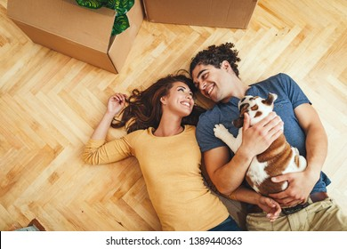 The young happy couple is moving into a new house. They are lying down on the floor with their little puppy after they brought boxes with things to their new home.