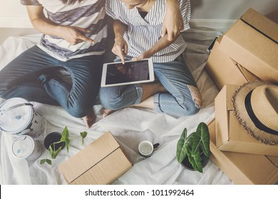 Young happy couple moving in new home, sitting and relaxing on the floor and shopping online with tablet