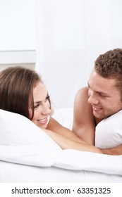 Young happy couple on the bed in the bedroom