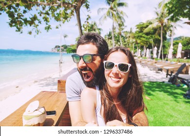 Young happy couple on honeymoon vacation amuse on tropical beach background in cafe. Build funny faces