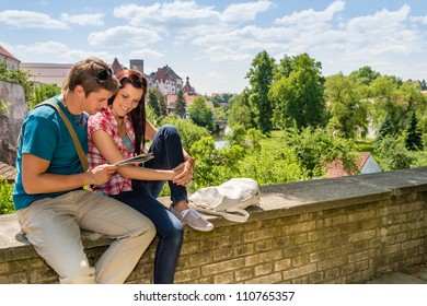 Young happy couple on vacation in city looking at map