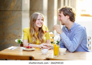 Young happy couple in the outdoor cafe