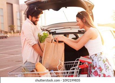 Young happy couple packing groceries in the trunk of the car from the supermarket
